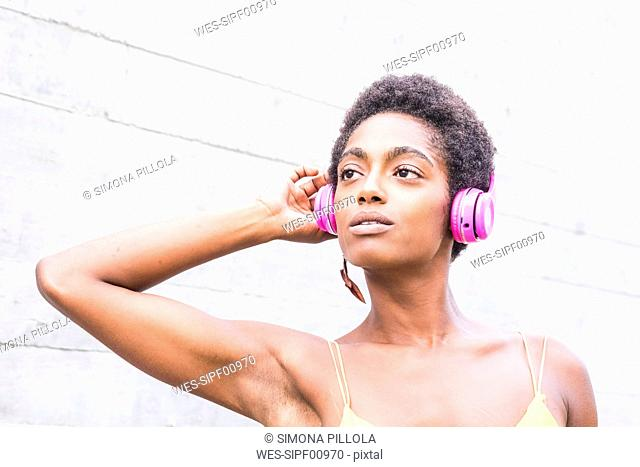 Portrait of woman listening music with pink headphones