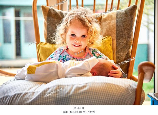 Female toddler and baby sister on chair, portrait