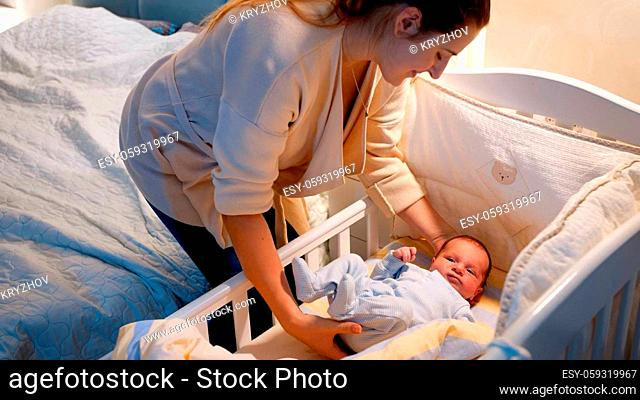 Beautiful young caring mother putting her newborn baby boy in crib and covering him with warm blanket at night. Concept of happy parenting and family happiness