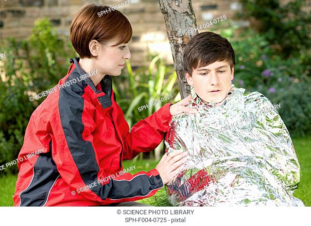 Hypothermia. Woman wrapping a boy in a foil blanket to warm him up