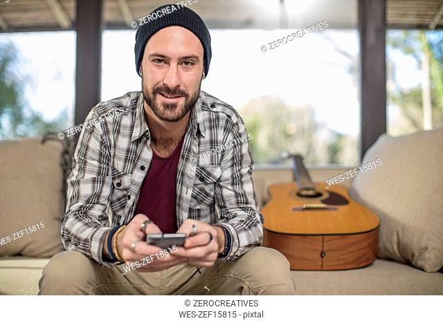 Portrait of smiling young man at home sitting on couch with guitar using cell phone