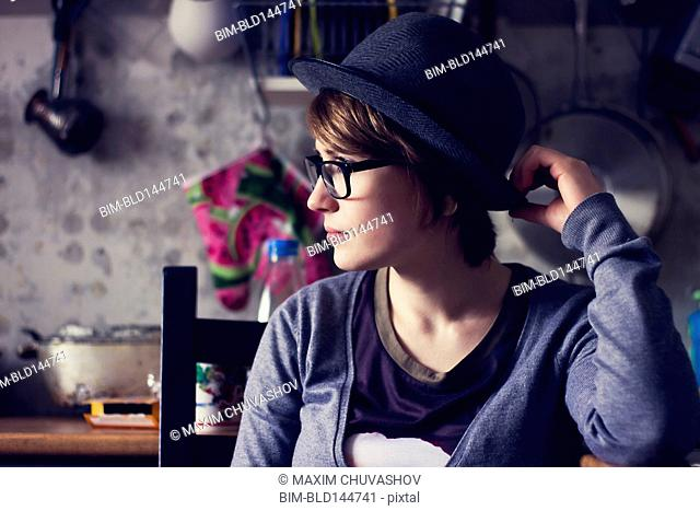 Caucasian woman wearing hat and eyeglasses in kitchen