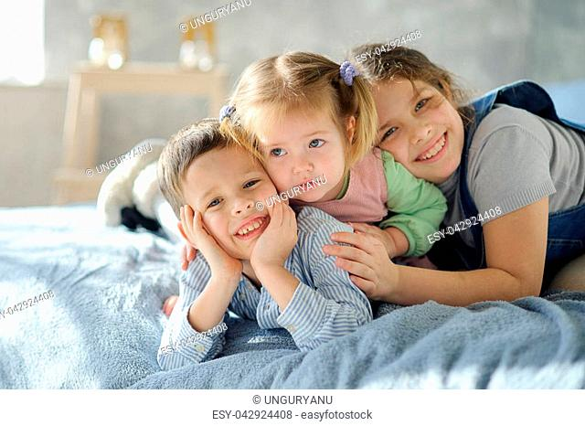 Two sisters and a brother. Three children from the same family are lying on the bed