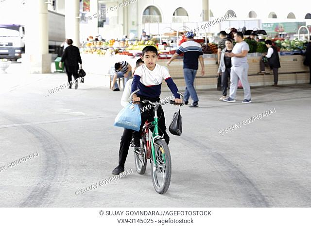 Tashkent, Uzbekistan - May 08, 2017: Two unknown kids riding on a bicycle in the main market place this morning