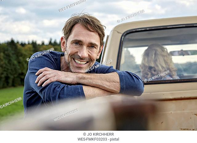 Portrait of smiling man at pick up truck
