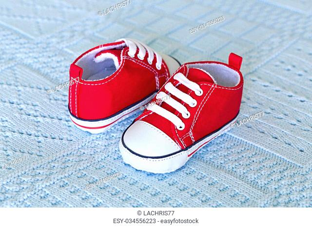 A pair of red baby shoes on a blue background