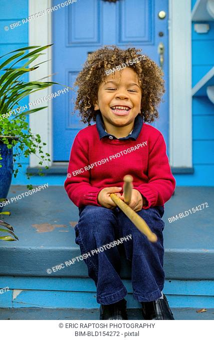 Pacific Islander boy with drumsticks sitting on front stoop