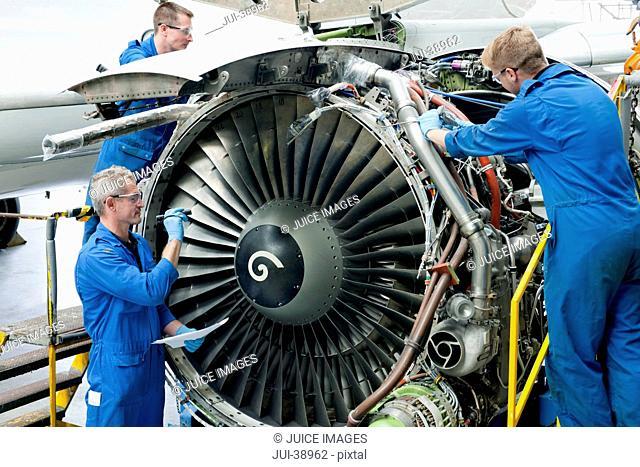 Engineers assembling engine of passenger jet in hangar