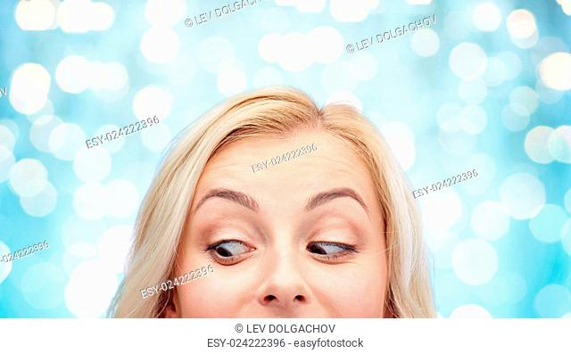 curiosity, advertisement and people concept - happy young woman or teenage girl face over blue holidays lights background