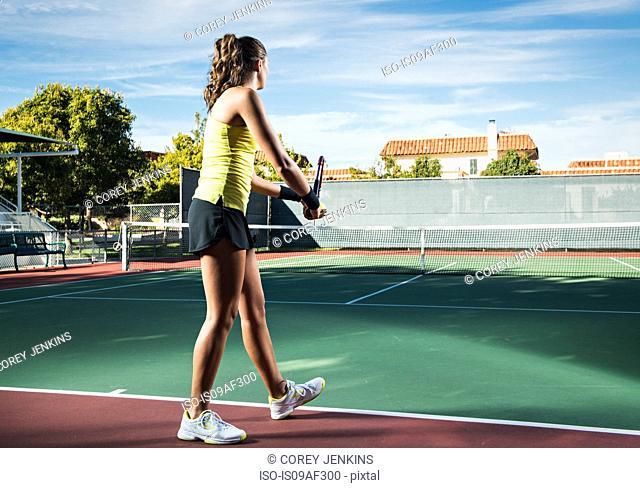 Female tennis player serving ball