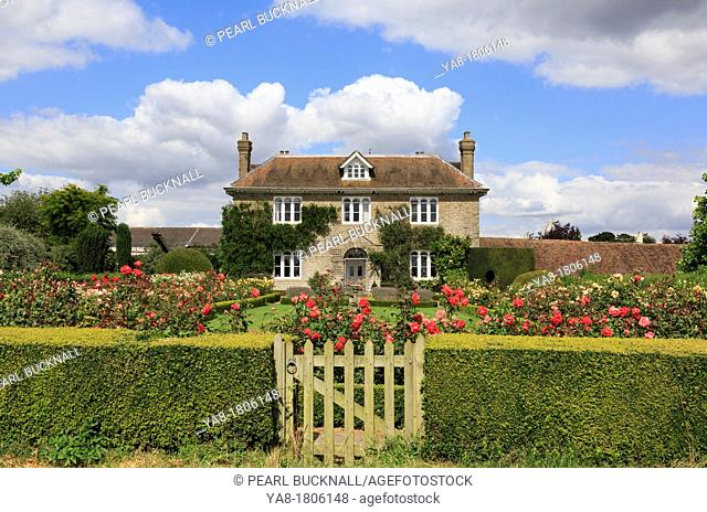 Pluckley, Ashford, Kent, England, UK, Britain, Europe  Hedge with gate to rose garden in front of an English country house 1816 in summer