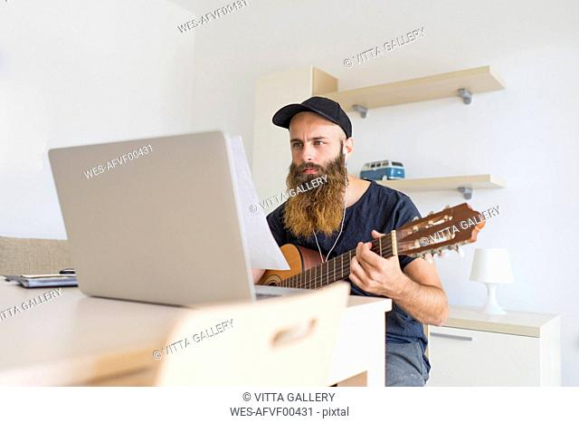 Serious young man at home with earphones and laptop playing guitar