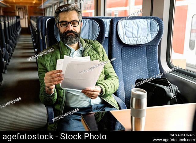Man sitting in train reading documents