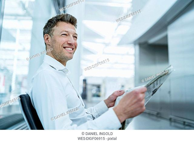 Smiling businessman sitting in waiting area with newspaper