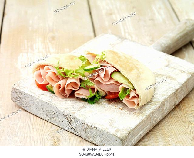 Wafer thin ham, salad leaves, tomato and cucumber on whitewashed cutting board