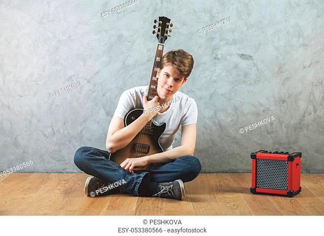 Portrait of caucasian man sitting on wooden floor with amplifier and guitar in hands. Concrete wall background. Music, concert, hobby, rehearsal