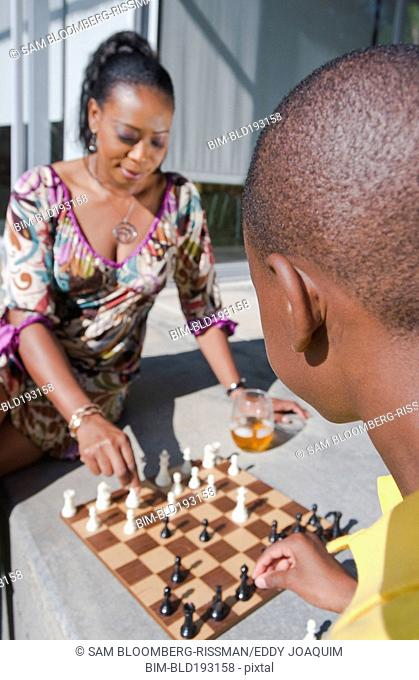 Black mother and son playing chess