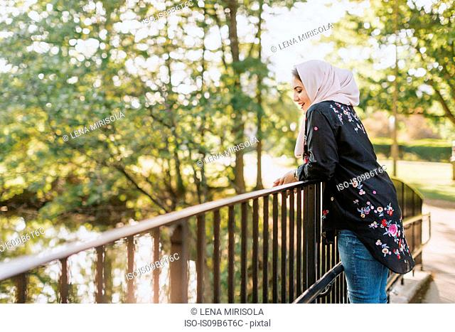 Young woman wearing hijab on bridge looking away at view