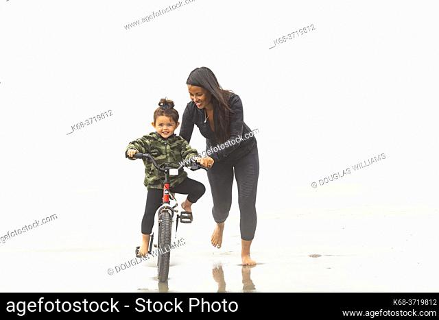 A three year old girl on her push bike, helped by her mother, on the beach at Tofino, BC, Canada