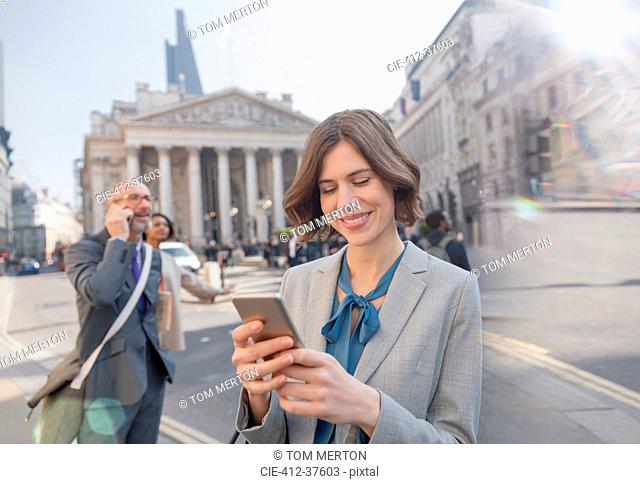 Businesswoman texting with cell phone on urban city street, London, UK