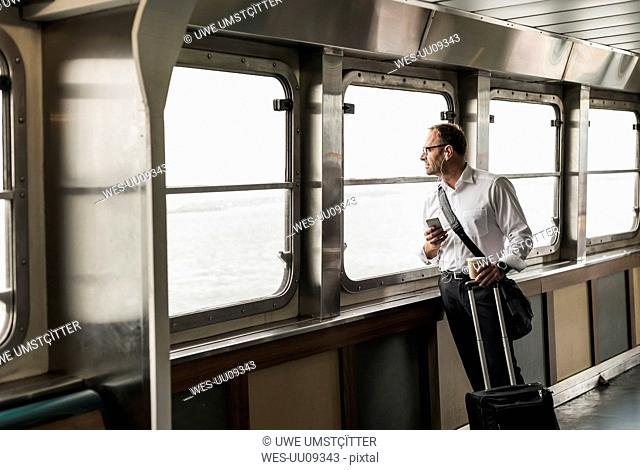 Businessman on a ferry looking out of window