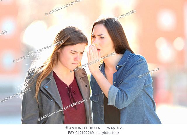Gossip woman telling secret to her angry friend in the street