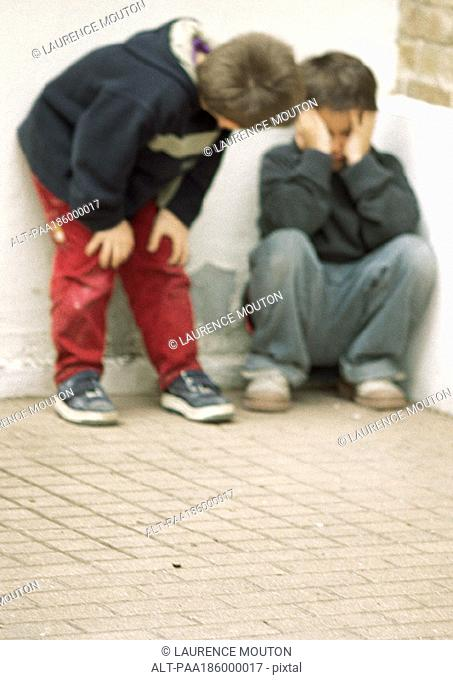 Two children in corner, one holding head