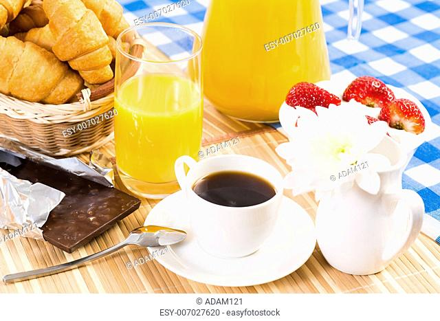 continental breakfast: coffee, strawberry with cream, croissant