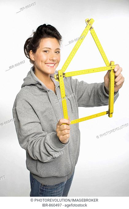Young woman smiling into the camera holding in her hands a yellow folding ruler folded in the shape of a house