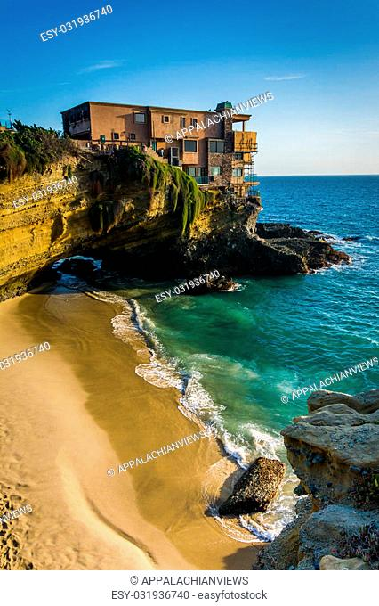 View of a house on a cliff and a small cove at Table Rock Beach, in Laguna Beach, California