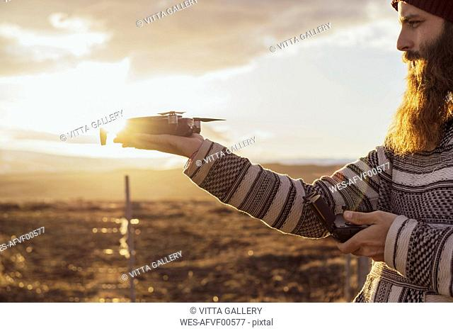 Iceland, bearded man holding a drone at sunset
