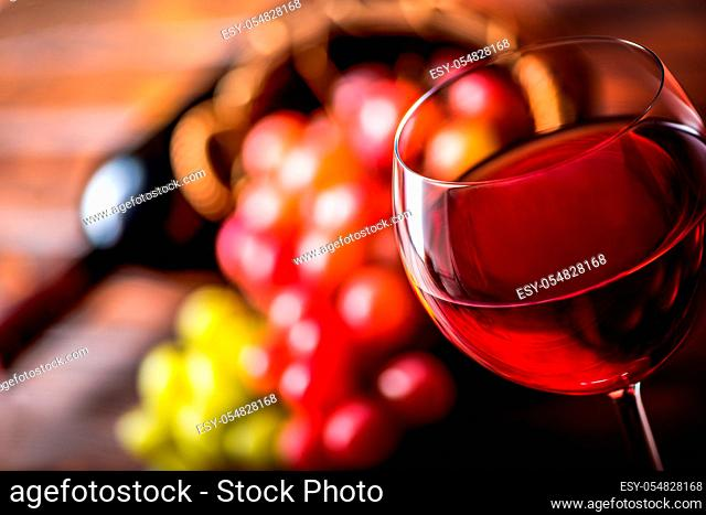 Wineglass with red wine on a background of grape and bottle on wooden table