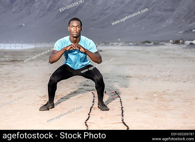 Full length serious black male athlete doing squats near ladder on sandy Famara Beach in Lanzarote, Spain