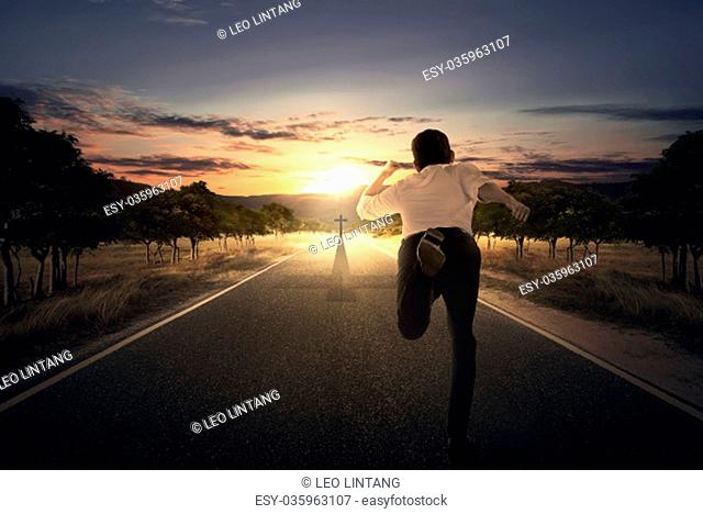 Man running chasing cross at the end of the road at sunset