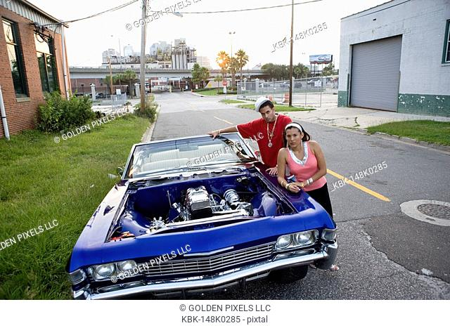 Portrait of a young hip-hop couple standing beside a pimped-up vintage car in depressed urban neighborhood