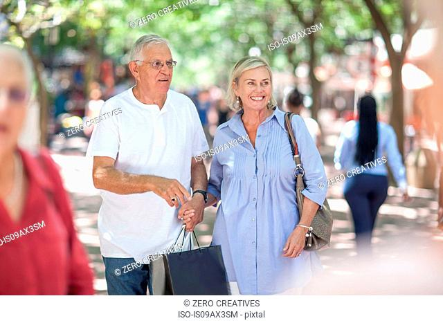 Senior man and woman holding hands shopping in city