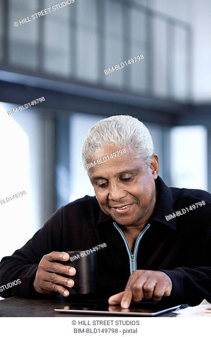 Black man drinking coffee and using digital tablet