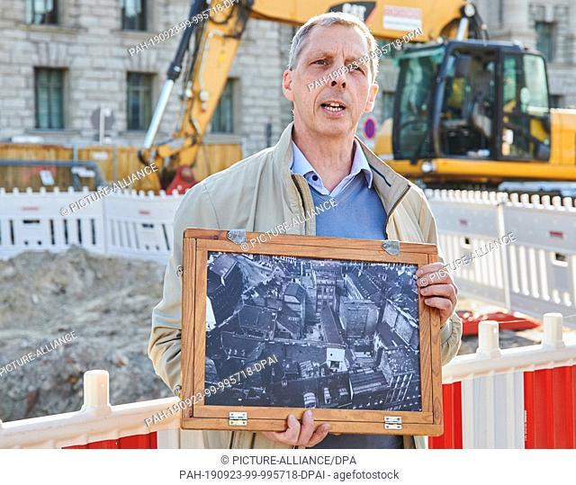 23 September 2019, Berlin: Project manager Michael Malliaris shows a picture from the twenties of the same area on which he stands