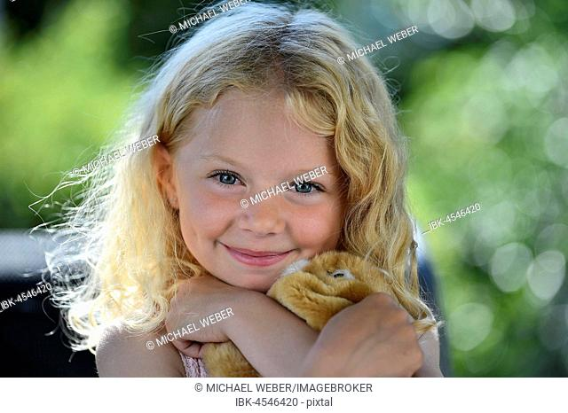 Little girl with blonde hair and cuddly toy, portrait, Sweden