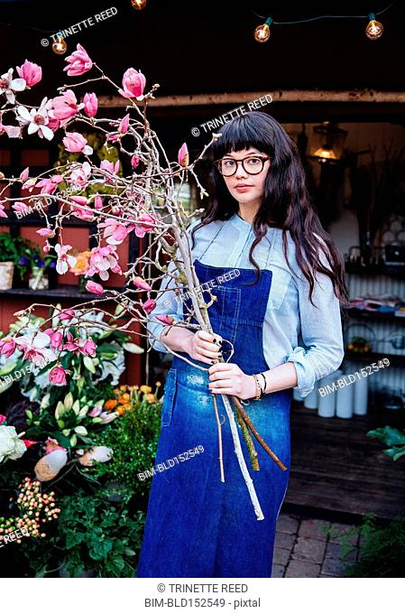 Mixed race florist carrying flowering branches