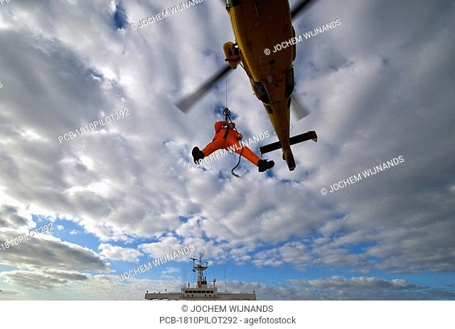 Marine pilot arriving by helicopter at the rendez vous point where a bulk carrier is waiting to be guided
