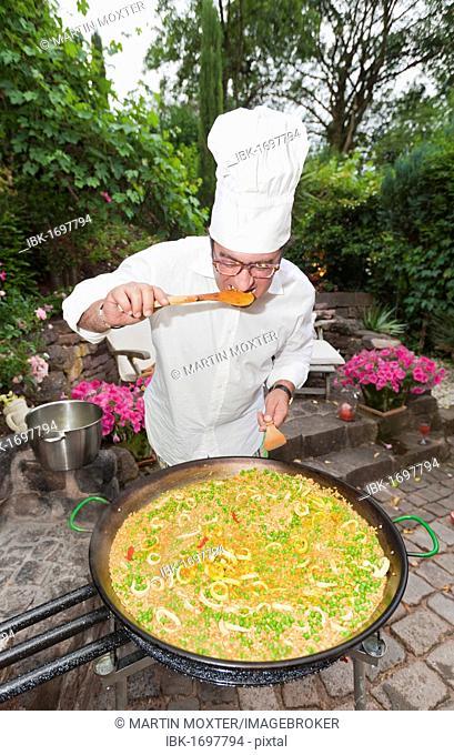 Cook preparing a paella, a Spanish rice dish, adding saffron, tasting, series, no. 1
