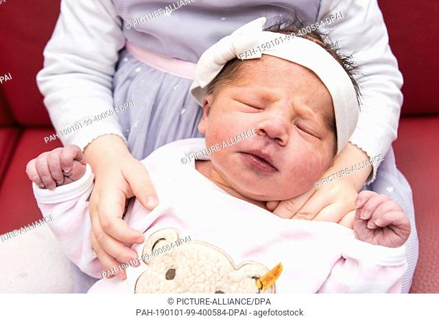 01 January 2019, Hamburg: Little Elena is being held by her sister Clara. Elena was the first New Year's baby of the year 2019 to see the light of day in...