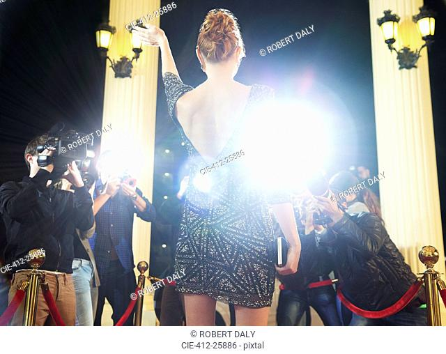 Celebrity waving to paparazzi photographers at red carpet event