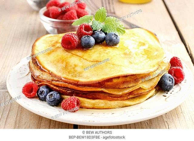 Stack of pancakes with syrup, raspberries and blueberries decorated with mint leaf. Party dessert