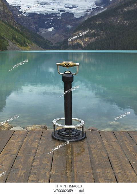 Binoculars overlooking still lake in rural landscape