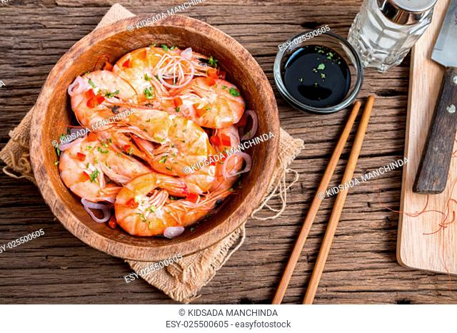 steamed shrimps in a wooden bowl on wood background