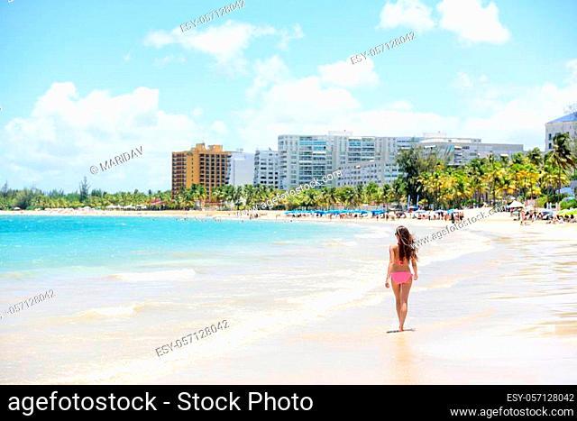 People on Isla Verde resort beach in Puerto Rico. Unrecognizable woman walking down the beach on summer holiday in bikini on famous Hispanic travel destination