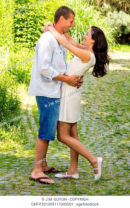 Joyful couple standing and hugging in park