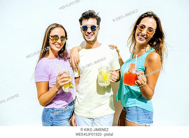 Happy friends holding refreshing drinks in front of white wall